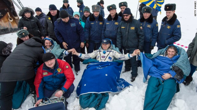 In this handout provided by NASA, Expedition 38 Flight Engineer Sergey Ryazanskiy of the Russian Federal Space Agency, Roscosmos, left, Commander Oleg Kotov of Roscosmos, center, and, Flight Engineer Mike Hopkins of NASA, sit in chairs outside the Soyuz TMA-10M capsule shortly after they landed in a remote area on March 11 near the town of Zhezkazgan, Kazakhstan.