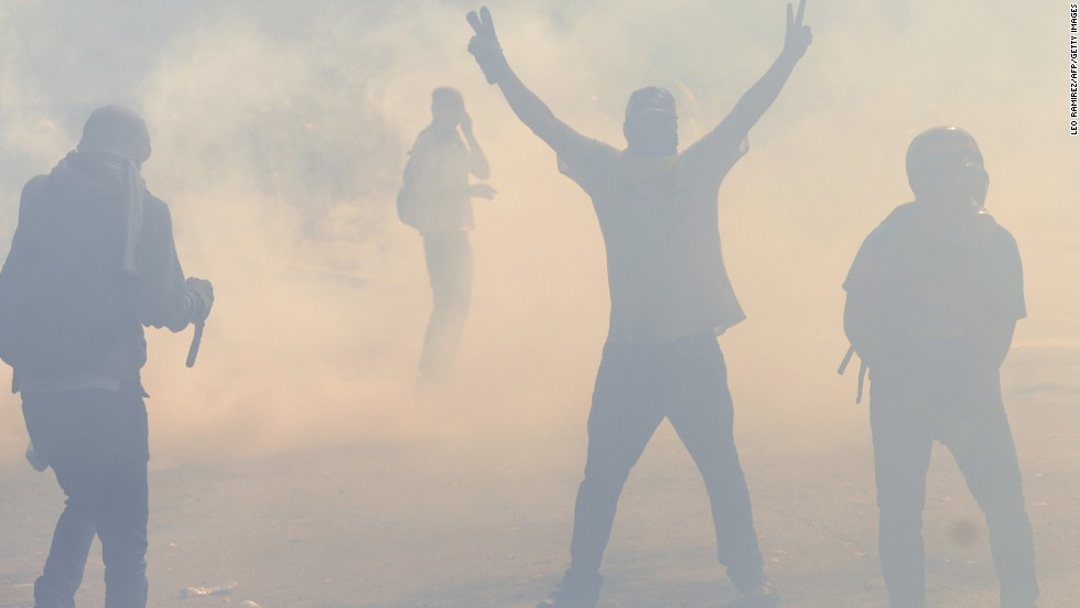 Students walk amid tear gas shot by riot police in Caracas on March 12.