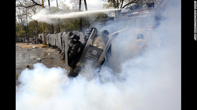 A riot policeman kicks back a tear gas bomb during a protest in Caracas on March 12.