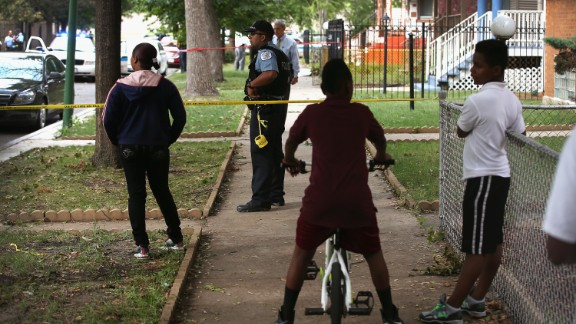 Family and friends watch police investigate the scene where a 14-year-old boy was shot and killed in September.