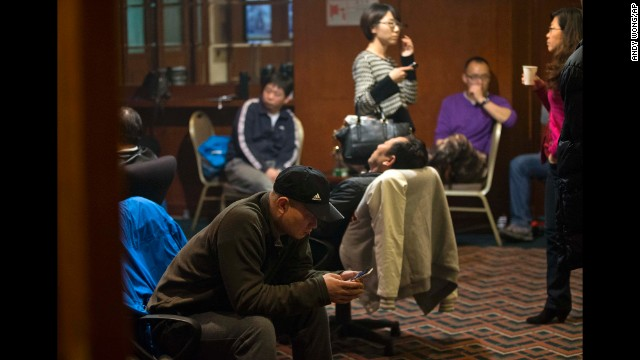 Relatives of missing passengers wait for the latest news inside a hotel room in Beijing on Wednesday, March 12.