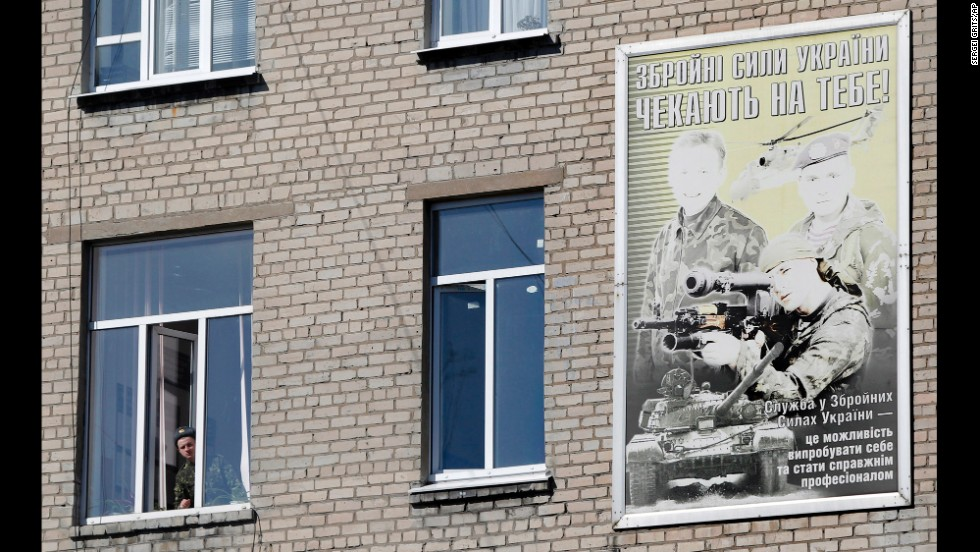 "A Ukrainian soldier looks out of the window of a regional military building with a poster reading ""Ukraine's armed forces wait for you!"" in Donetsk on March 13."