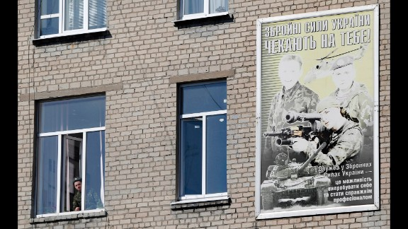 "A Ukrainian soldier looks out of the window of a regional military building with a poster reading ""Ukraine"