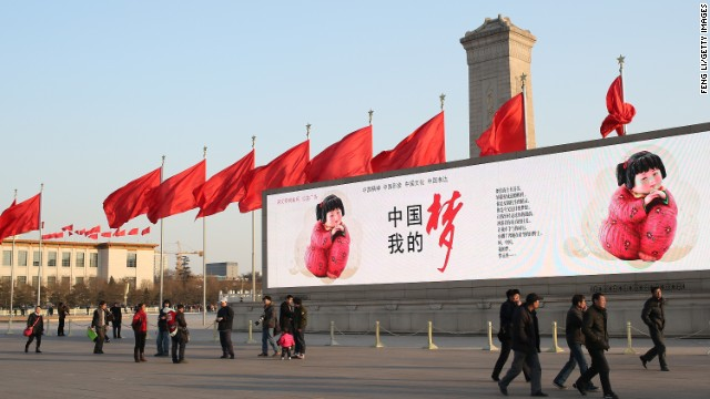 "In Beijing, citizens walk by a large banner reading ""Chinese dream."""