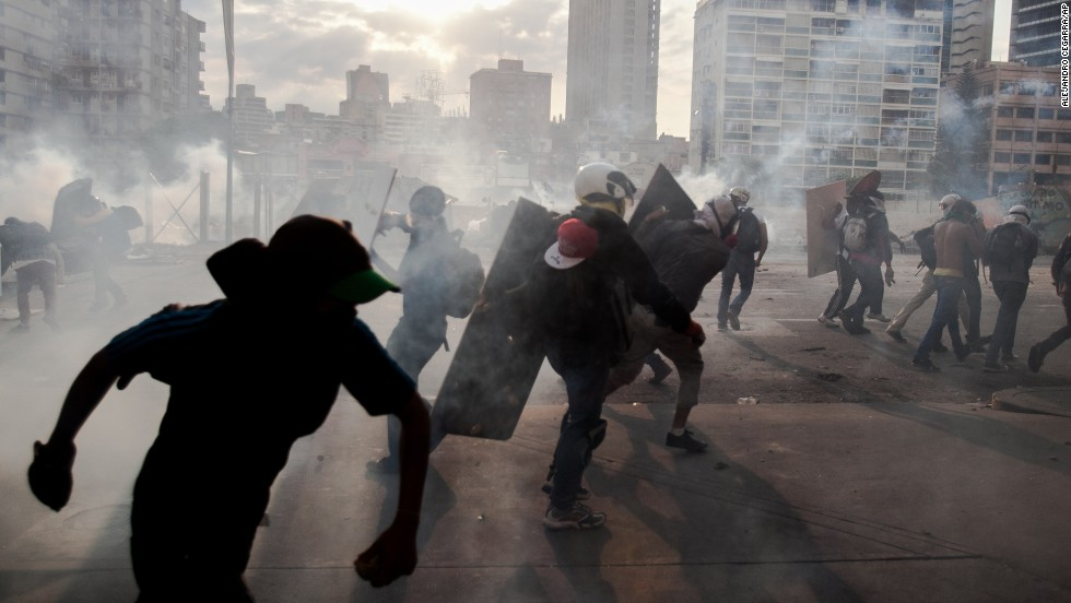"Anti-government protesters take cover from tear gas during clashes with police Monday, March 10, in Caracas, Venezuela. It has been a month since <a href=""http://www.cnn.com/2014/02/18/world/gallery/venezuela-protests/index.html"">violent clashes in the country</a> first grabbed global attention, and demonstrators have shown no sign of backing down."