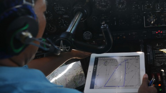 A pilot on board a Vietnamese Air Force Russian-made AN-27 uses a map to help search Vietnam