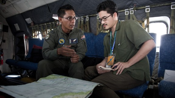 TO GO WITH: MALAYSIA-CHINA-VIETNAM-MALAYSIAAIRLINES-TRANSPORT-ACCIDENT,FOCUS BY SHANNON TEOH  This picture taken on March 15, 2014 shows Royal Malaysian Air Force Navigator captain Izam Fareq Hassan (L) explaning to Agence France-Presse correspondent Shannon Teoh on board a Malaysian Air Force CN235 during a search and rescue (SAR) operation to find the missing Malaysia Airlines flight MH370 plane over the Strait of Malacca. The disappearance of a Malaysia Airlines passenger jet is a potential disaster for a national flag carrier already struggling to cauterise severe financial hemorrhaging in the face of intensifying industry competition, raising the spectre of costly lawsuits and a drop in bookinngs. AFP PHOTO / MOHD RASFANMOHD RASFAN/AFP/Getty Images