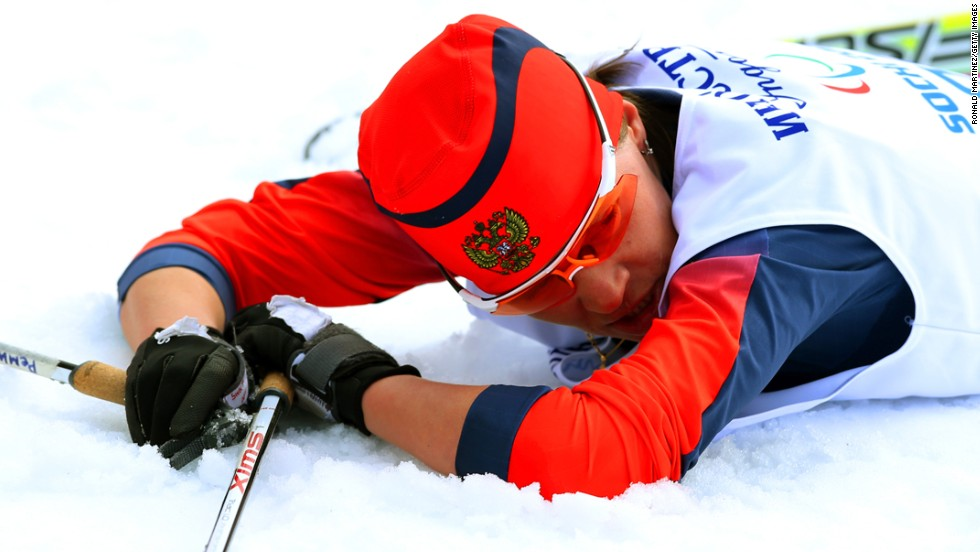 Gold medalist Elena Remizova of Russia collapses after crossing the finish line in the women's cross-country 5-kilometer free visually impaired event.