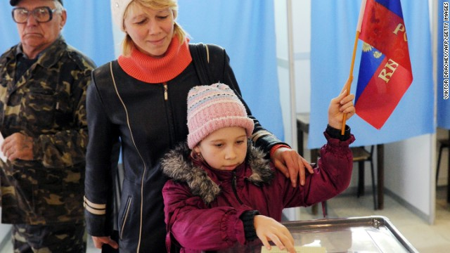 A child casts her mother's ballot while holding a Russian flag at a polling station on March 16, 2014 in Simferopol.