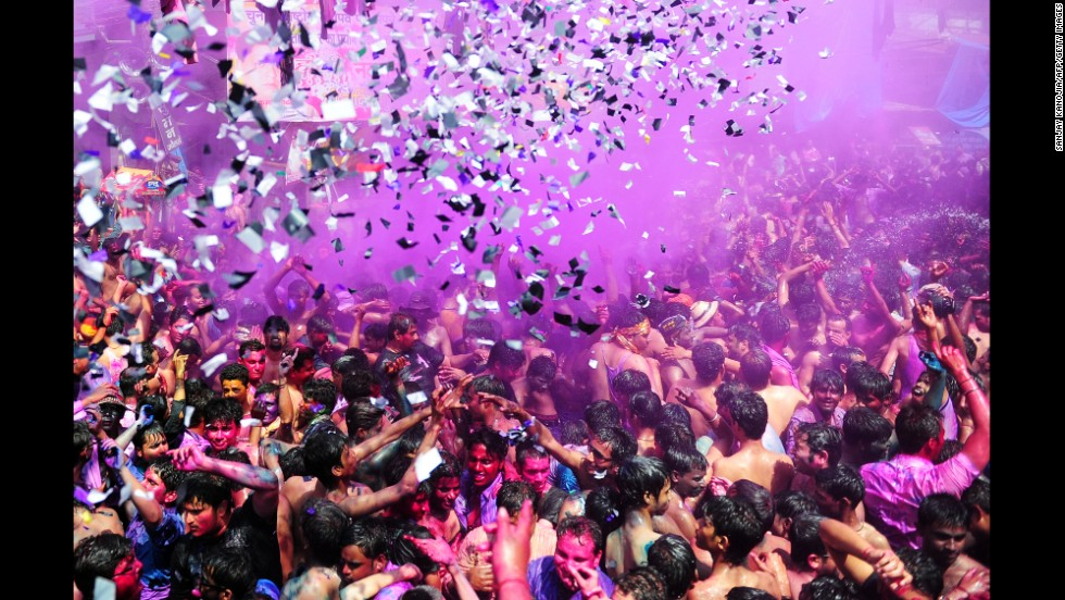 People covered in colored powder dance during celebrations in Allahabad on March 17.