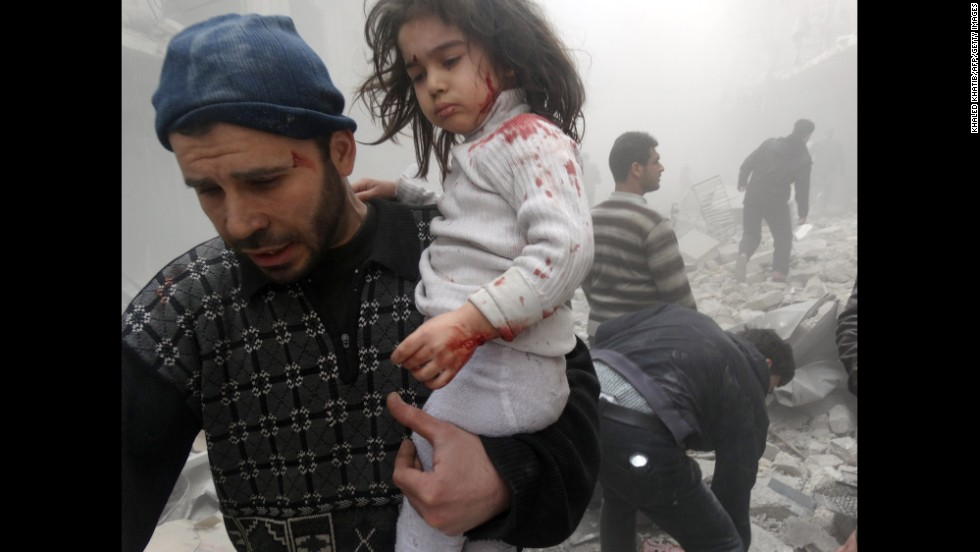 "A man carries a child who was found in the rubble of a building in Aleppo, Syria, after it was reportedly hit by a barrel bomb dropped by government forces on Monday, March 18. The United Nations estimates more than 100,000 people have been killed since <a href=""http://www.cnn.com/2014/02/10/middleeast/gallery/syria-unrest-2014/index.html"">the Syrian conflict</a> began in March 2011."
