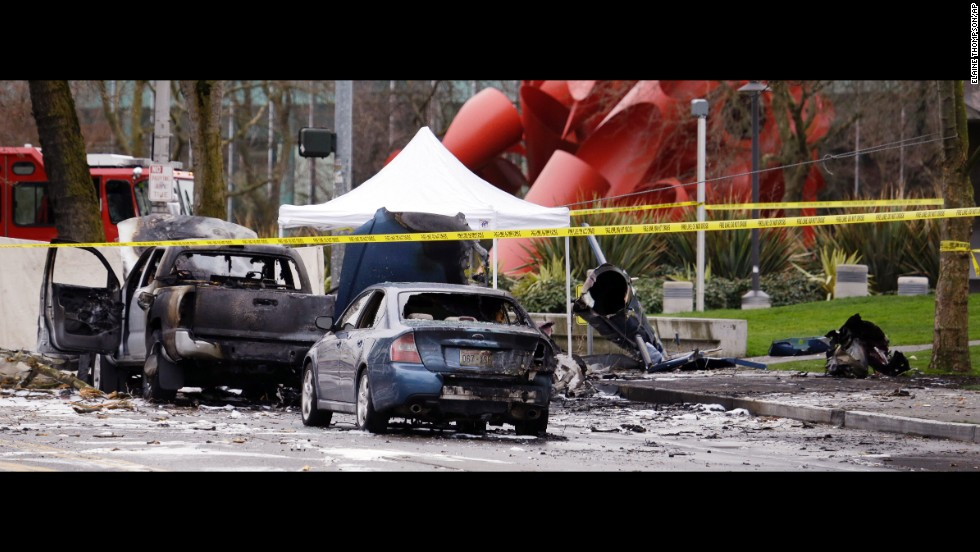 Caution tape surrounds the charred wreckage of a news helicopter and two vehicles after the helicopter crashed onto a street near Seattle's Space Needle on Tuesday, March 18. Both people inside the helicopter died, and a third person was critically injured on the ground, a spokesman for the Seattle Fire Department said.