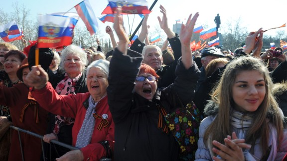 People react as they listen to a speech of Russian president broadcast on a giant screen in Sevastopol, on March 18, 2014.
