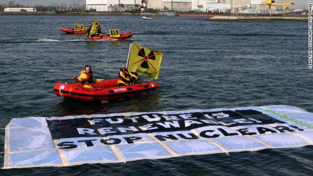 Greenpeace hold banners in boats in front of the nuclear power plant of Fessenheim on March 18, 2014.
