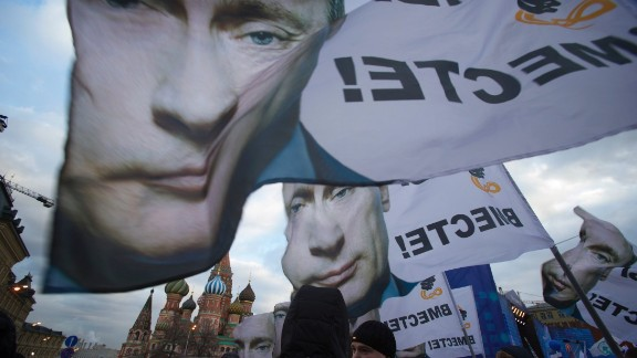 """People rally in support of Crimea joining Russia, with banners and portraits of Russian President Vladimir Putin, reading """"We are together,"""" in Red Square in Moscow, Tuesday, March 18, 2014."""
