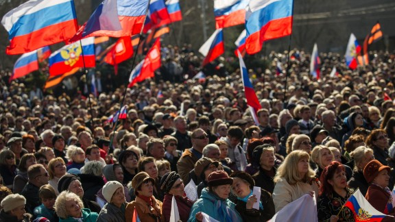 """People gather at a square to watch a televised address by Russian President Vladimir Putin to the Federation Council, in Sevastopol, Ukraine, Tuesday, March 18, 2014. Putin on Tuesday fiercely defended Russia's move to annex Crimea saying Crimea's vote on Sunday to join Russia was in line with """"democratic norms and international law."""""""