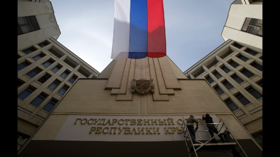 A Russian flag waves as workers install a new sign on a parliament building in Simferopol, Crimea