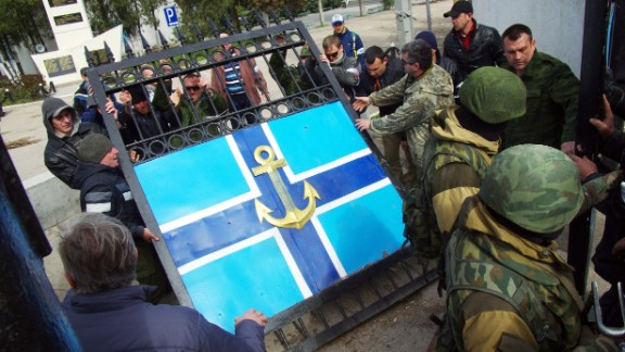 Pro-Russian protesters remove the gate to the Ukrainian navy headquarters as Russian troops stand guard in Sevastopol on Wednesday, March 19.