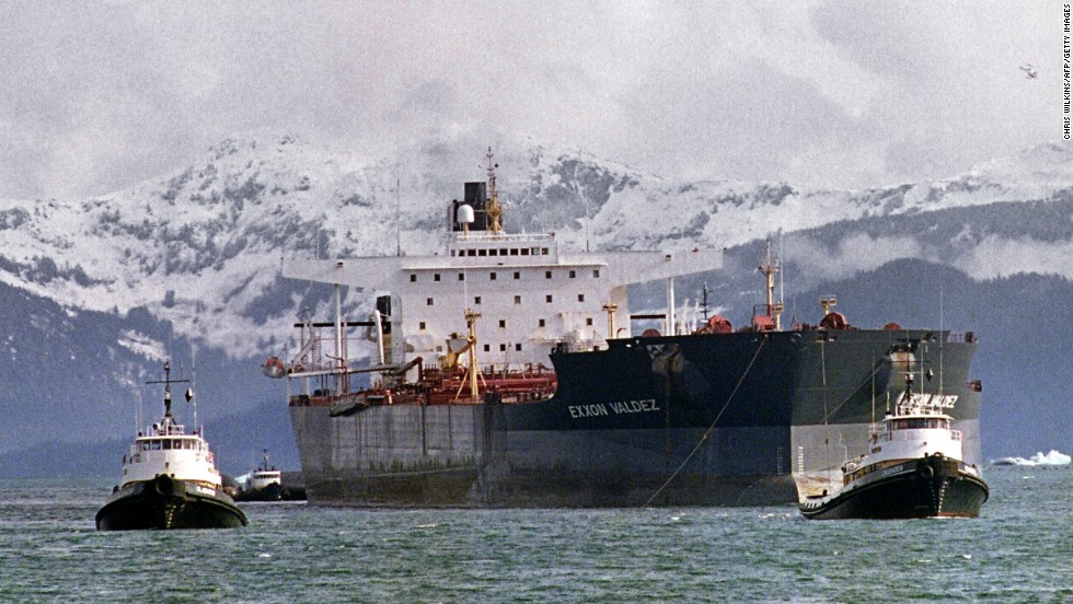 Tugboats tow the Exxon Valdez off Bligh Reef to a harbor for repair and salvage efforts, two weeks after the beginning of the oil disaster. The tanker changed names and owners several times, and was bought in 2012 by an Indian company, which scraps ships for steel and spare parts.