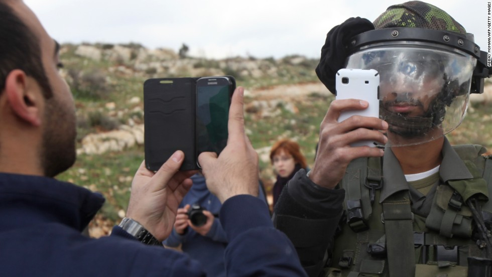A Palestinian man and a member of Israel's security forces take pictures of each other Friday, March 14, after a demonstration in the West Bank village of Nabi Saleh.