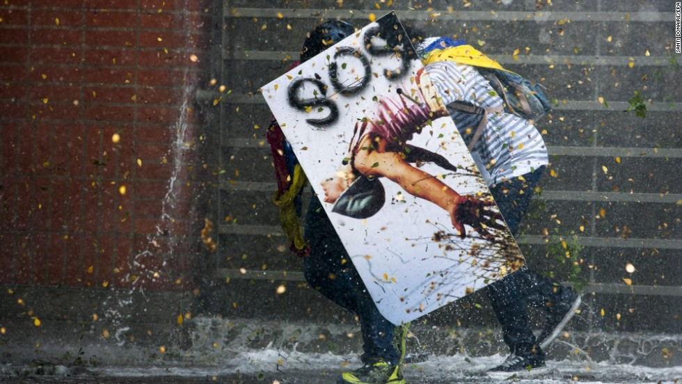 Demonstrators clash with members of the National Police after a mass meeting called by opposition students in Caracas on Thursday, March 20.