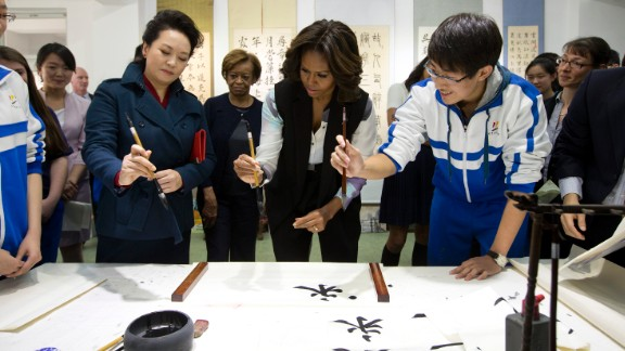 """Peng Liyuan, wife of Chinese President Xi Jinping, left, shows first lady Michelle Obama how to hold a writing brush as they visit a Chinese traditional calligraphy class in Beijing on Friday, March 21. The first lady is on <a href=""""http://www.cnn.com/2014/03/21/politics/gallery/michelle-obama-china/index.html"""">an official visit</a> to expand relations between the United States and China. Click through the gallery to see her other international travels through the years."""