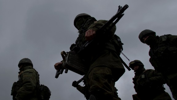 Pro-Russian soldiers march outside an Ukrainian military base in Perevalne, Crimea, Thursday, March 20, 2014.