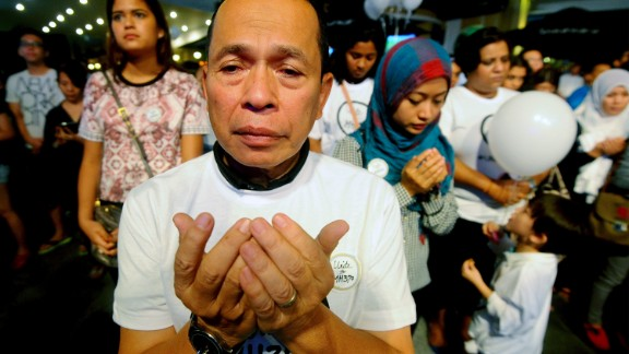 In this picture taken on Tuesday, March 18, 2014 a Malaysian Muslim man prays during an interfaith event for the missing Malaysia Airlines flight MH370 at a shopping mall in Petaling Jaya outside Kuala Lumpur, Malaysia.