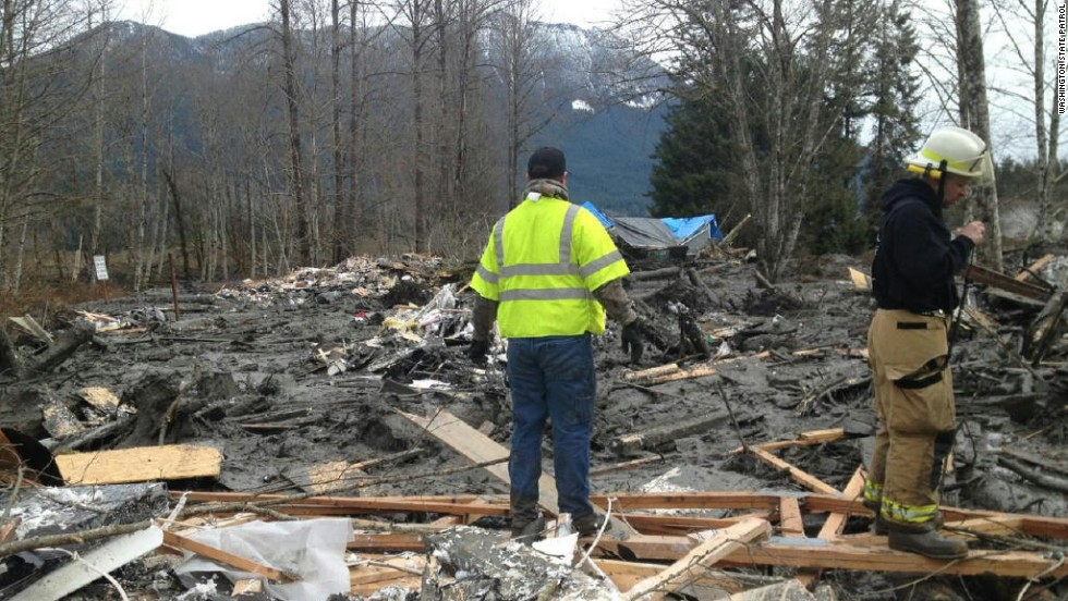 Emergency workers arrive at the scene of the landslide on Saturday, March 22.