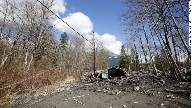 Downed powerlines and parts of a destroyed house can be seen in the debris blocking the road near Oso, Washington on March 23.