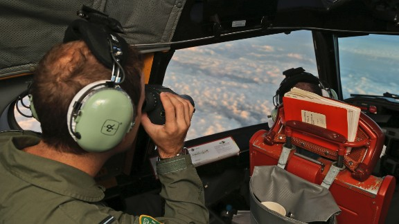 """Crew aboard an Australian P-3 Orion """"sub hunter"""" scan the southern Indian Ocean as they search for the missing plane on March 23."""