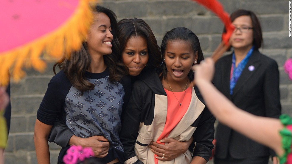 Obama hugs Sasha, right, and Malia as they watch dancers perform in Xian on March 24.