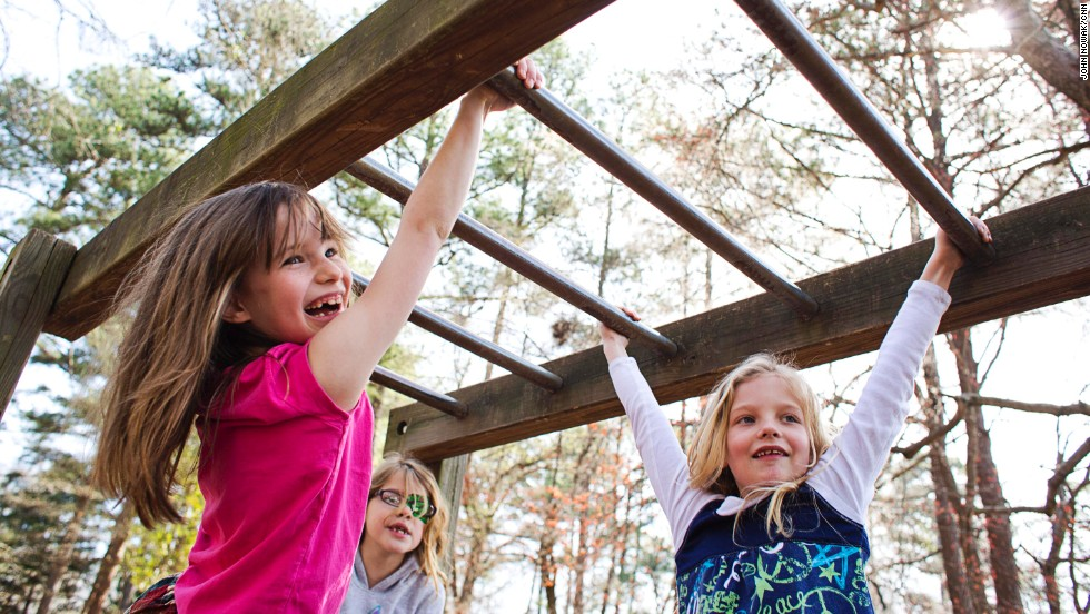 Students swing from the monkey bars at Hess Academy in Decatur, Georgia. Physical education and movement are key parts of the curriculum at the private school.