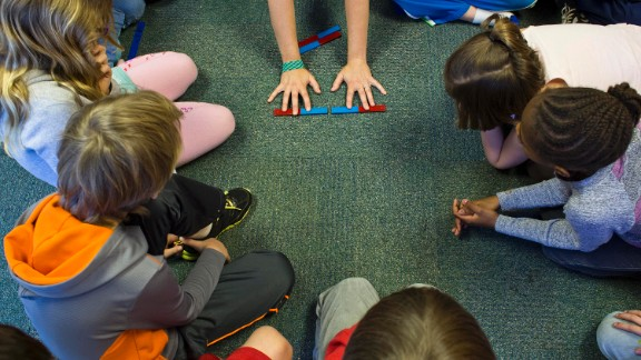 Students learn about the properties of magnets while sitting in a circle on the floor. Hess Academy students are encouraged to move as much as they need while doing their classwork.