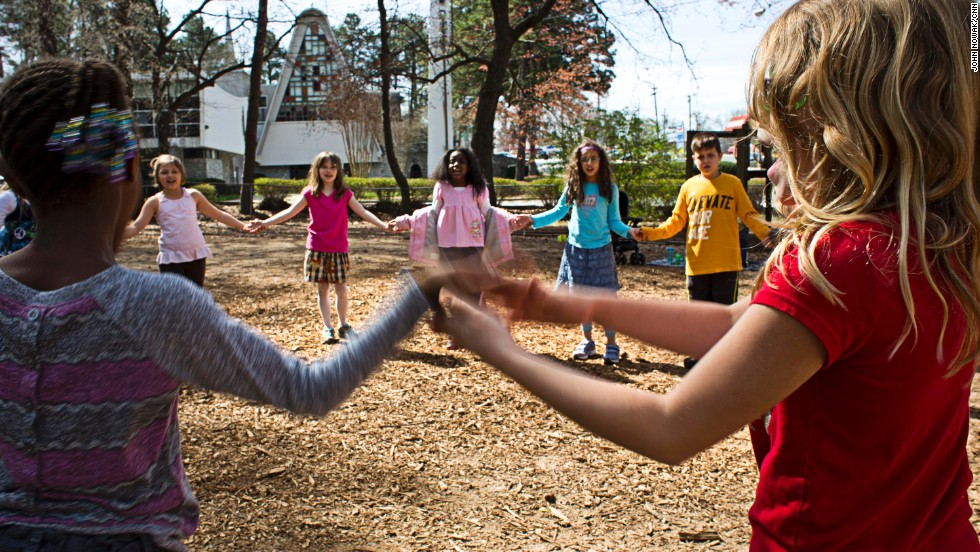 Students join hands while playing a game outside. Many days begin and end on the school's playground.
