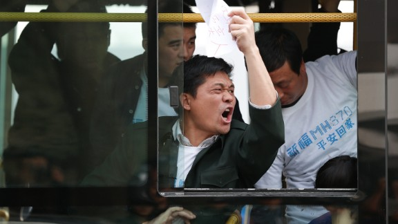 Chinese relatives of the flight MH370 gesture in protest as they sit on the bus waiting to go to the Malaysian embassy on March 25, 2014 in Beijing, China.