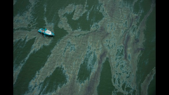 A vessel surrounded by a sheen of oil floats near Galveston on Sunday, March 23.