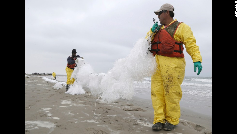 After a weekend boat collision caused 168,000 gallons of oil to spill into the Port of Houston, cleanup workers spread viscous snare line to snag oil Monday, March 24, along East Beach in Galveston, Texas.
