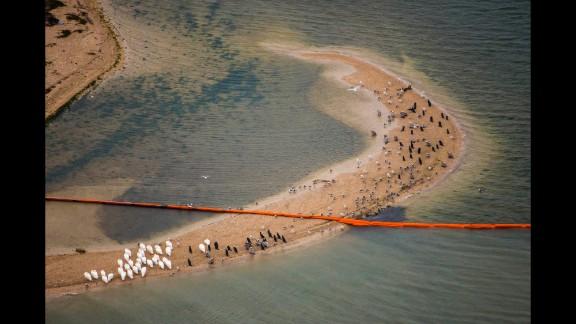 Oil booms cut across a sand bar on Galveston's Pelican Island on March 23.