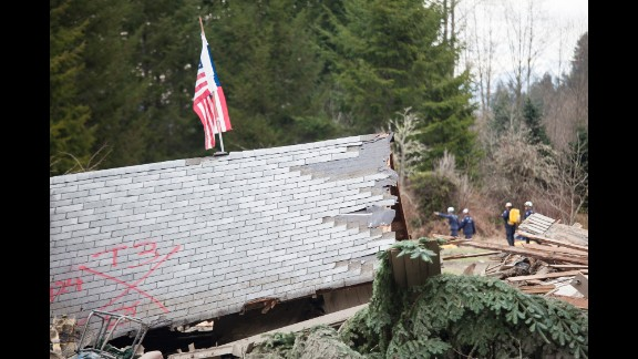 The roof of a house sits among debris as emergency personnel continue to look for survivors on March 25.