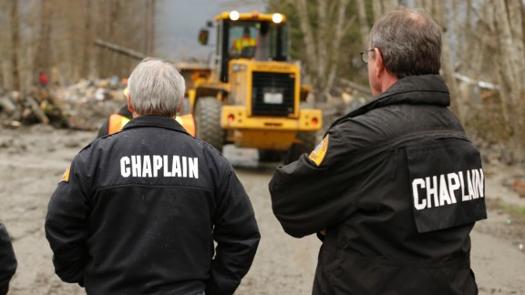 Chaplains watch as crews clear debris from State Route 530 in Oso on March 25.