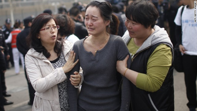 A relative of passengers on the missing Malaysia Airlines flight MH370 cries as she participates in a protest outside the Malaysian embassy in Beijing on March 25, 2014.