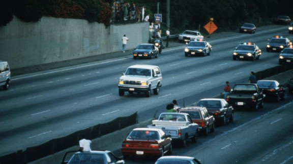 Motorists stop and wave as police cars pursue the white Ford Bronco on June 17, 1994.