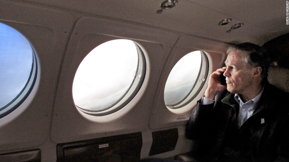 Washington Gov. Jay Inslee speaks on the phone with a victim's family member as he flies to the Snohomish County Emergency Operations Center in Everett on March 26.