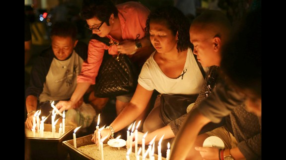 People in Kuala Lumpur light candles during a ceremony held for the missing flight