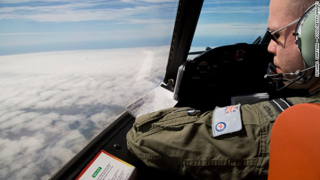 Flight Lieutenant Jayson Nichols looks out of the cockpit of a Royal Australian Air Force AP-3C Orion aircraft over cloud while searching for missing Malaysian Airlines flight MH370 over the southern Indian Ocean on March 27, 2014 off the coast of Perth, Australia.