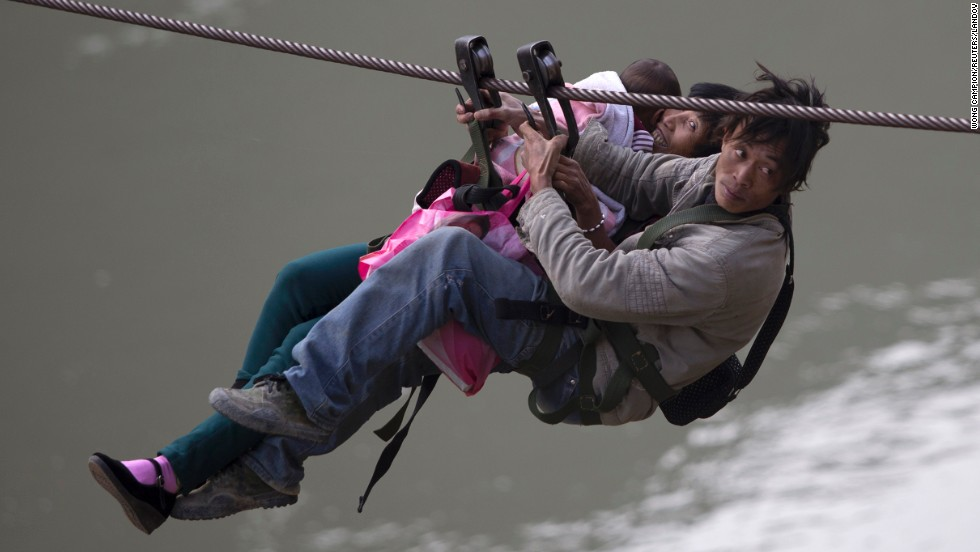 A man, his wife and their child use a zip line to cross the Nujiang River in China on Saturday, March 22. Residents of the Nujiang Lisu Autonomous Prefecture have been using the zip line for years to cross the river, as there is no bridge nearby, according to local media.