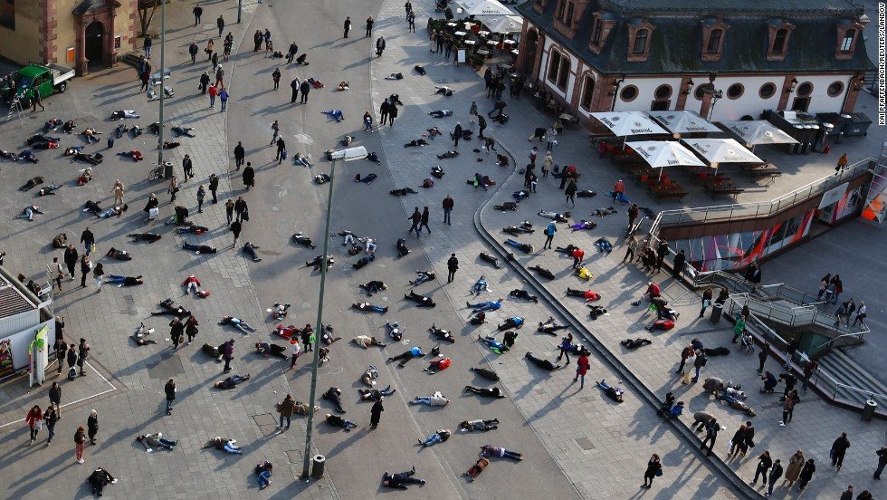 People lie down in Frankfurt, Germany, on Monday, March 24, as part of an art project to remember the 528 victims of the Katzbach concentration camp.
