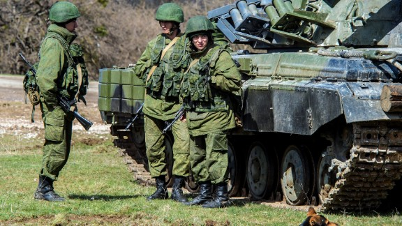 Russian soldiers stand near a tank outside a former Ukrainian military base in Perevalnoye, near the Crimean capital Simferopol, on March 27, 2014.