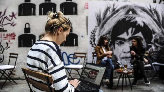 A woman uses a laptop computer showing Youtube's logo on March 27, 2014 in Istanbul, near a poster Berkin Elvan, the 15-year-old boy who died nine months after he was hit by a tear gas canister while going to buy bread during the 2013 protests in Istanbul. Turkey on March 27 banned video-sharing website YouTube, a week after blocking access to Twitter, after both were used to spread audio recordings implicating the prime minister in corruption, local media reported. AFP PHOTO / OZAN KOSE (Photo credit should read OZAN KOSE/AFP/Getty Images)